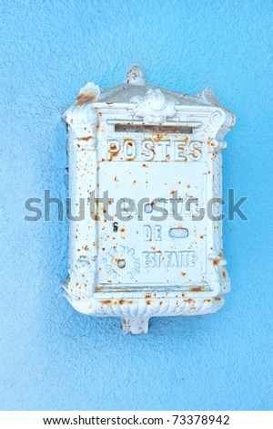 An antique mailbox from France mounted on a blue stucco wall - stock photo