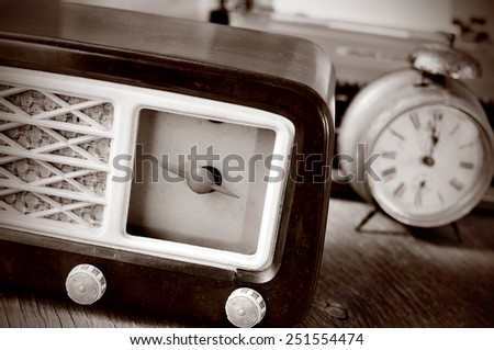 an antique radio receptor and some other antiques, such an alarm clock and a typewriter in the background, in sepia toning - stock photo