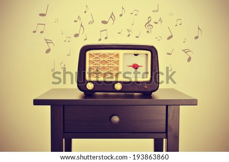 an antique radio receptor on a desk and musical notes, with a retro effect - stock photo