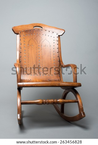 An antique rocking chair for a toddler. Photographed in the studio with a gray backdrop. - stock photo