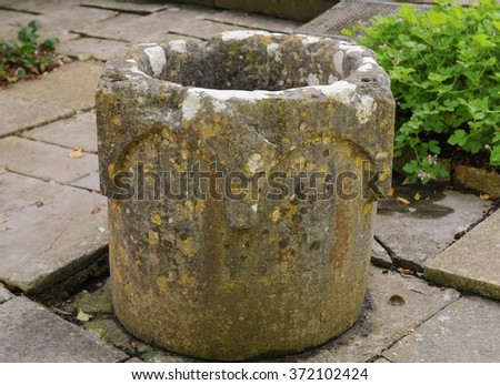An Antique Stone Pot in a Country Cottage Garden in the Rural Village of Tintinhull in Somerset, England, UK - stock photo