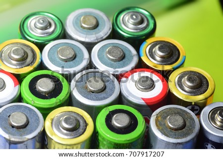 An appearance colorful reflective surface of used battery, anode side, AA size, 1.5 v.  Both recharge and non rechargeable. close up.