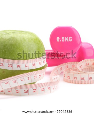 An apple, a measuring tape and dunbbells, closeup
