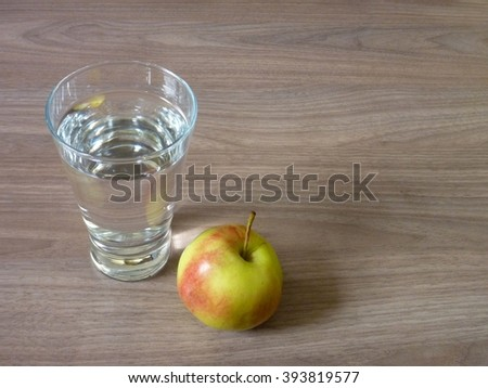 an apple and a glass of pure water