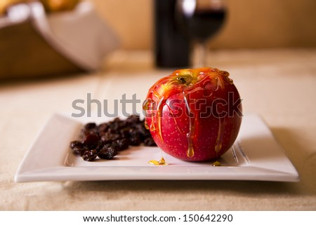 An apple drizzled with honey and raisins in a plate representing the sweetness of Rosh Hashanah - stock photo