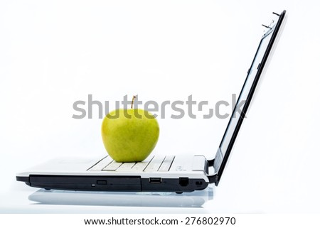 an apple is on the keyboard of a computer. symbolic photo for healthy and vitamin-packed snack. - stock photo