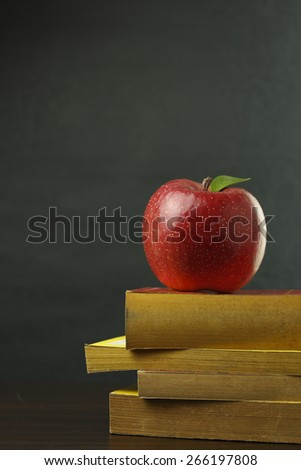 An apple on a stack of books next to a blank chalk board for copyspace. - stock photo
