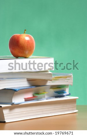 An apple on a stack of books on the teachers desk