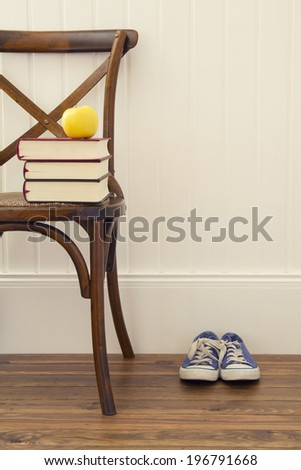 An apple on a stack of books over a chair. A pair of blue sneakers. - stock photo