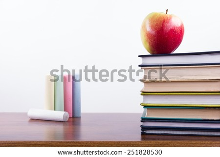 An apple on a stack of colorful books and chalk. Back to school. - stock photo
