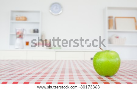 An apple on a tablecloth in a kitchen - stock photo