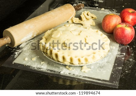 An apple pie with decorated crust apples and rolling pin - stock photo