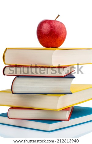 an apple sits on a pile of books. symbolic photo for healthy and vitamin-rich food in the school break. - stock photo