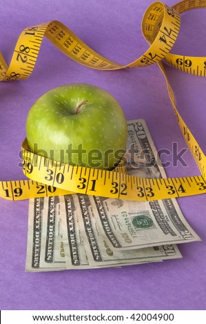 An apple, tape measure, and American currency represents the concept of measuring the cost of healthcare, food, or education.  Can also work for concept of the cost of healthcare, education or food. - stock photo