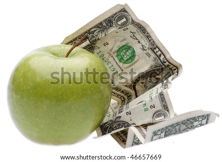 An apple with money symbolizes the cost involved in food, education, or healthcare. - stock photo