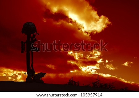An AR-15 rifle with combat helmet and boots silhouetted against a stormy sky as a memorial to a fallen soldier. - stock photo