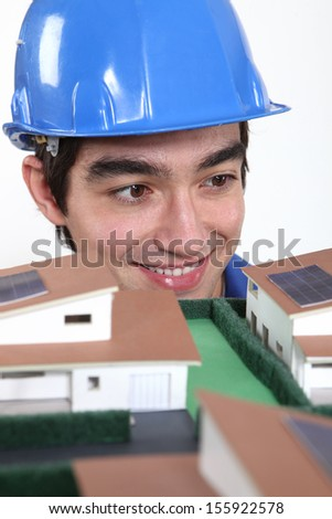 An architect fascinated by a miniature. - stock photo