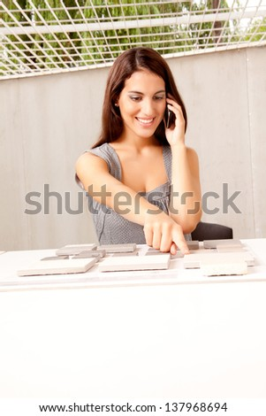 An architect on the phone choosing a stone tile swatch - stock photo