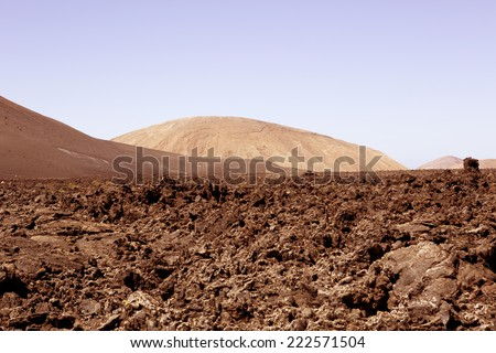 An arid desert or volcanic landscape. Possibly another planet