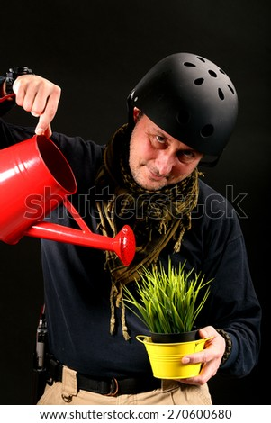 an armed man watering plant in a pot - stock photo