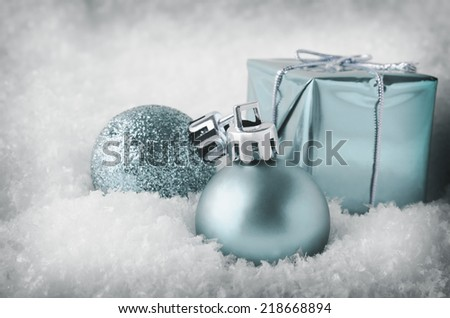 An arrangement of pale blue Christmas decorations sinking into soft, white artificial snow.  Includes glitter and matte  baubles and gift box.Cool, pale hues with a vintage vignette. - stock photo