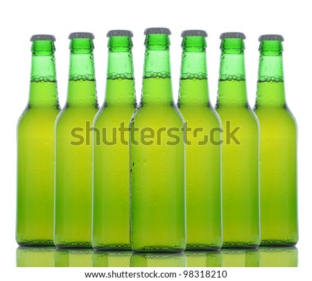 An arrangement of seven green beer bottles with reflection over a white background.