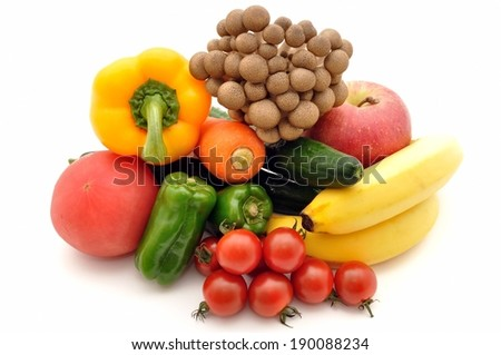 An arrangement of vegetables and fruits including an apple, banana, peppers, tomatoes and a carrot. - stock photo