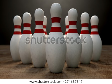 An arrangement of white and red used vintage bowling pins resting on a wooden bowling alley surface on a dark background