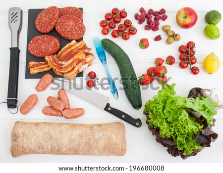an arrangment of barbecue ingredients with raw meat salad and fresh bread with utensils on a rustic white table top - stock photo