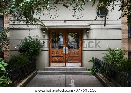 an art deco building entrance with old wooden door - stock photo