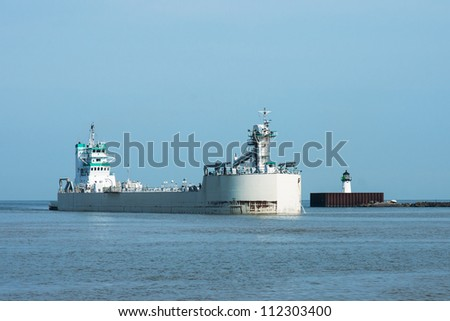 An articulated tugboat and barge entering the harbor a Cleveland, Ohio - stock photo