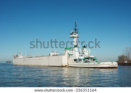 An articulated tugboat and barge running in reverse prepare to move upbound on the Cuyahoga River in Cleveland, Ohio - stock photo