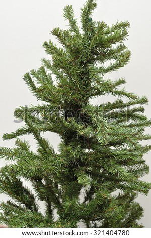 An artificial Christmas tree with no decorations isolated against a white background