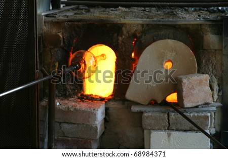 An artisan's furnace in a small Venetian studio where they are blowing a glass vase. The bright orange furnace is heating to over 1,000 degrees to melt the glass. - stock photo