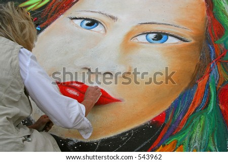 An artist creates her work in chalk on the pavement at the I Madonnari Italian Street Painting Festival at the Santa Barbara Mission in California. - stock photo