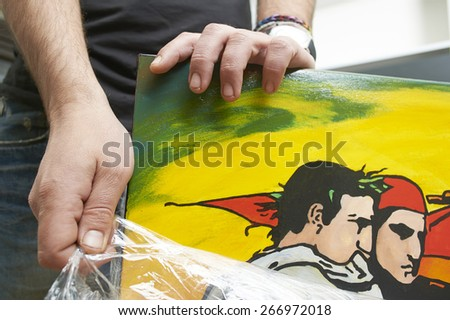 An artist removing ?ellulose package from his painting - stock photo