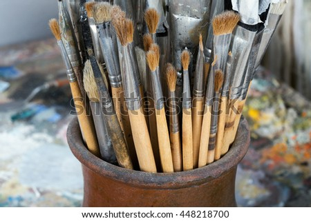 An artist's brushes covered with dust in studio - stock photo