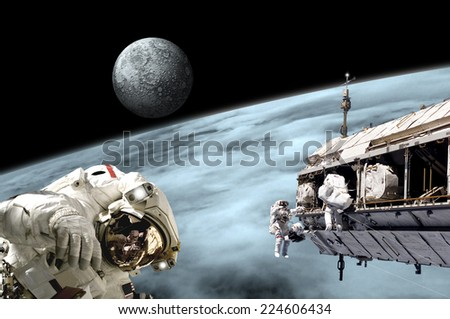 An artist's depiction of  a team of astronauts performing work on a space station while orbiting a large, alien planet as a large moon rises. Elements of this image furnished by NASA. - stock photo