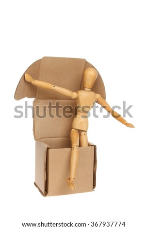 An artist's wooden manikin steps out of a brown cardboard box isolated against white - stock photo