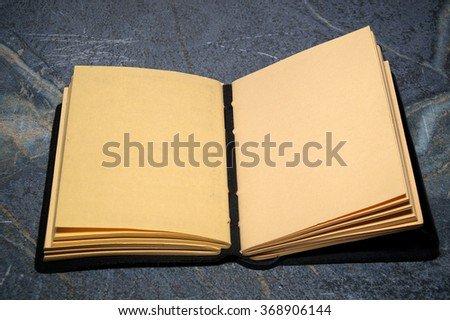 An artist sketchbook or writer notebook is open on soapstone table with both facing pages blank.