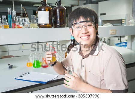 An Asia scientific researcher holding at a liquid solution in a lab. - stock photo