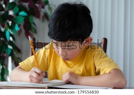 An Asian boy doing his homework at home. - stock photo