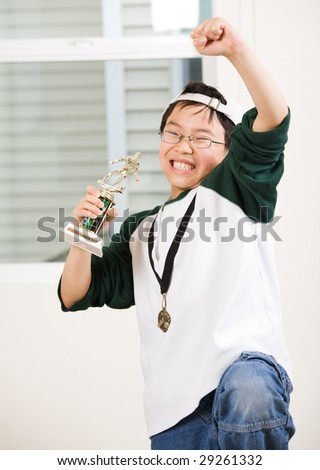 An asian boy excited about his winning sport medal and trophy