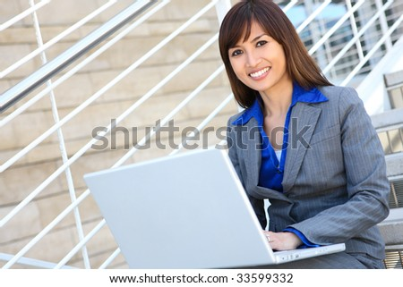 An asian business woman on stairs at office with laptop computer - stock photo