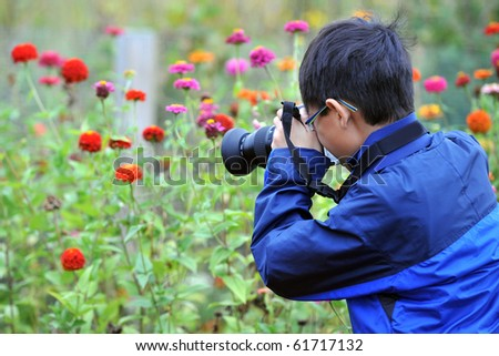 An Asian Child photographing flowers - stock photo