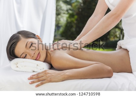 An Asian Chinese woman relaxing outside at a health spa while having a massage treatment - stock photo