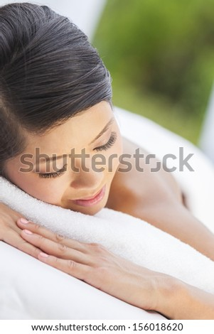 An Asian Chinese woman relaxing outside at a health spa while having a treatment or massage with a natural green background. - stock photo
