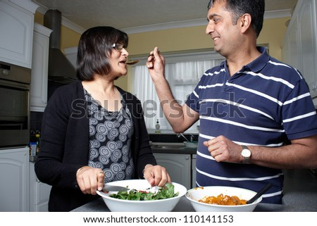 An Asian couple tasting food in the kitchen