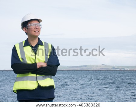 An asian engineer standing in front of the long bridge across the ocean - stock photo