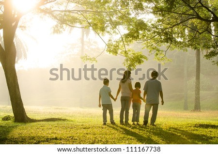 an asian family walking in the park during a beautiful sunrise, backlight - stock photo